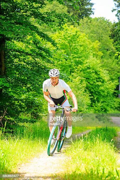 若い男が乗ってマウンテンバイク