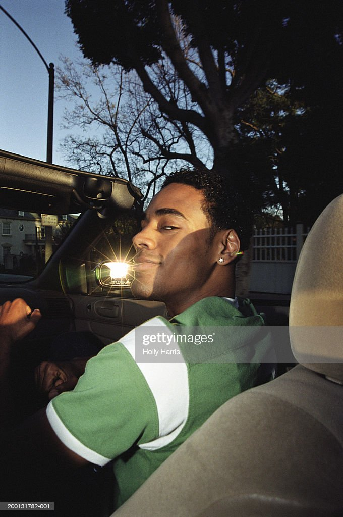 Young man riding in convertible car : Stock Photo