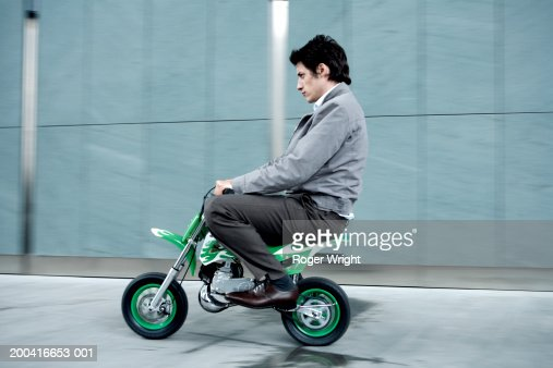 Young man riding miniture motorbike, side view (blurred motion)
