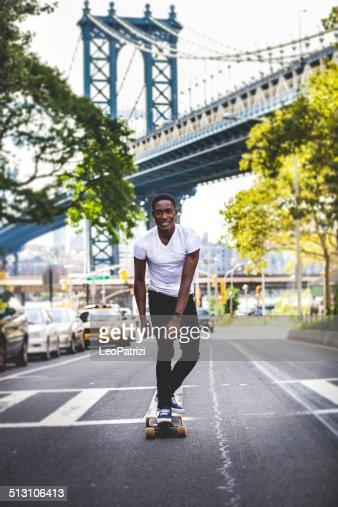 Jeune homme à cheval longboard dans les rues de New York