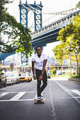 Young man riding on longboard in New York streets