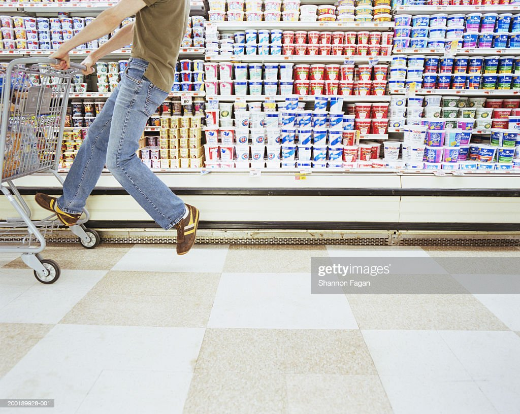Young man riding shopping cart in supermarket, low section, side view : Stock Photo