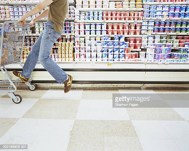 Young man riding shopping cart in supermarket, low section, side view