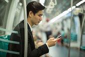 Young man riding the subway, looking at his phone.