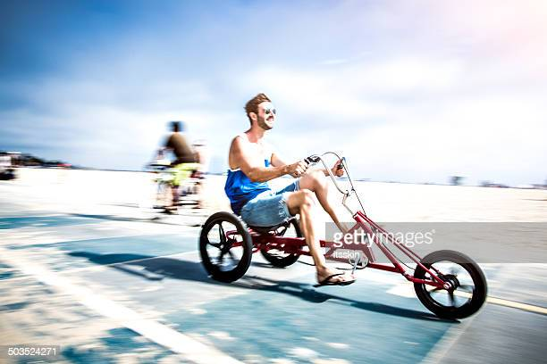 Young man riding tricycle bicycle in LA