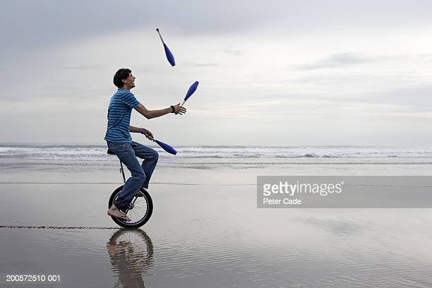 Young man riding unicycle while juggling