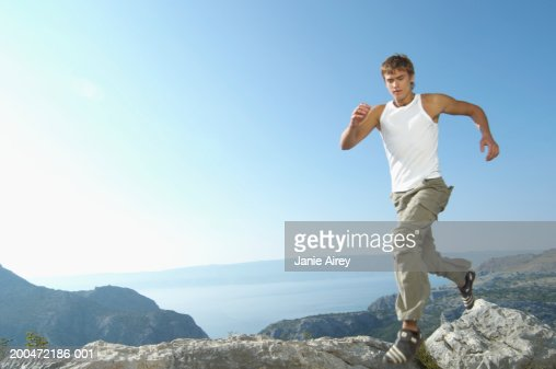 Young man running across rocks in mountain landscape : Stock Photo