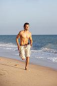 Young Man Running Along Summer Beach