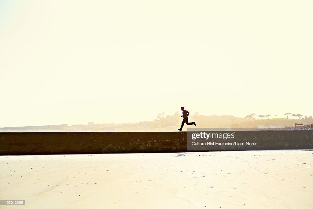 Young man running along wall, silhouette : Stock Photo