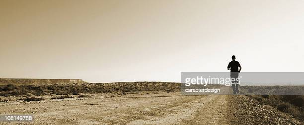 Giovane uomo che corre lungo la strada nel deserto, Viraggio seppia