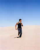 Young man running down sand dune, looking over shoulder