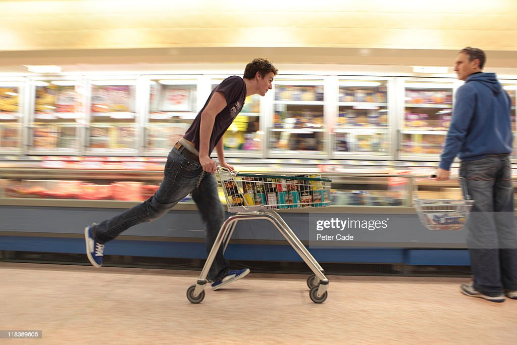 Young man running in supermarket with trolly : Stock Photo
