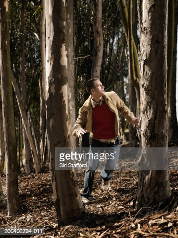 Young man running in woods : Stock Photo