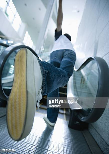 Young man running up escalator
