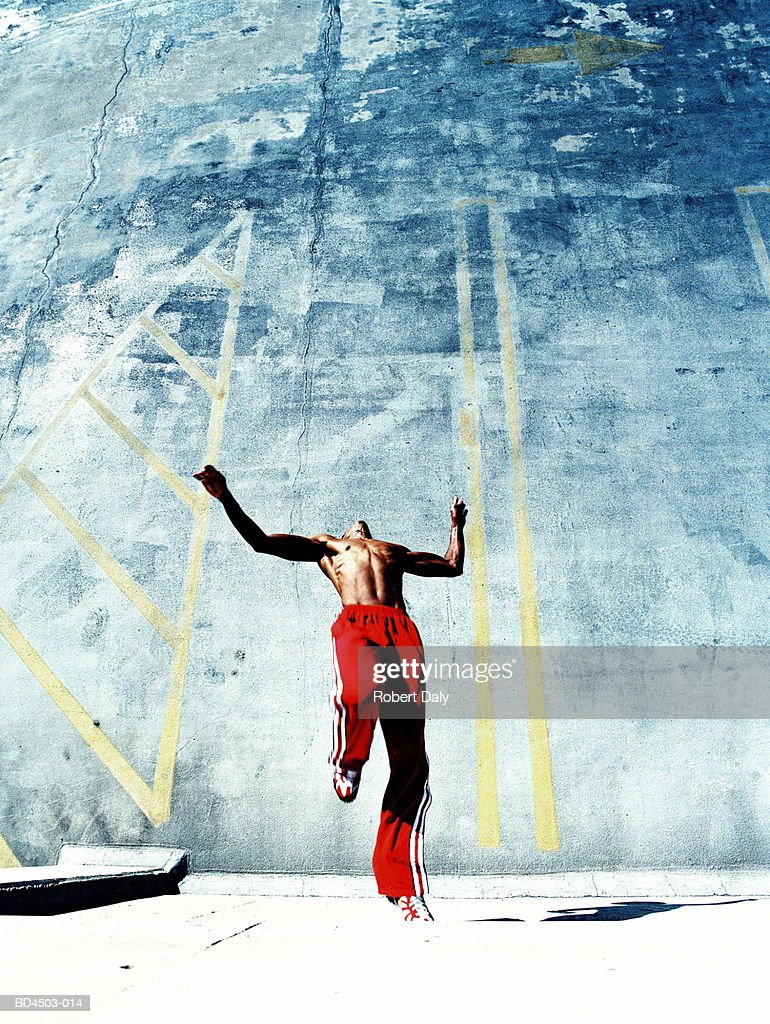Young man running up wall in rooftop car park, elevated view : Stock Photo