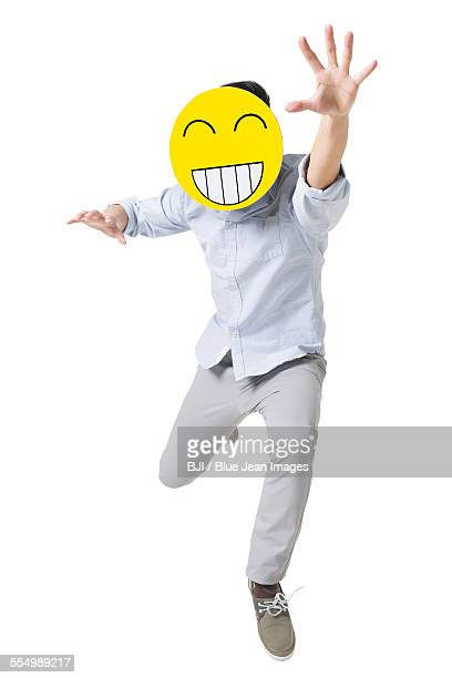 Young man running with a happy emoticon face in front of his face