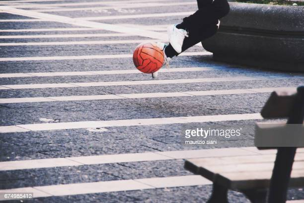 Young man running with soccer ball in street