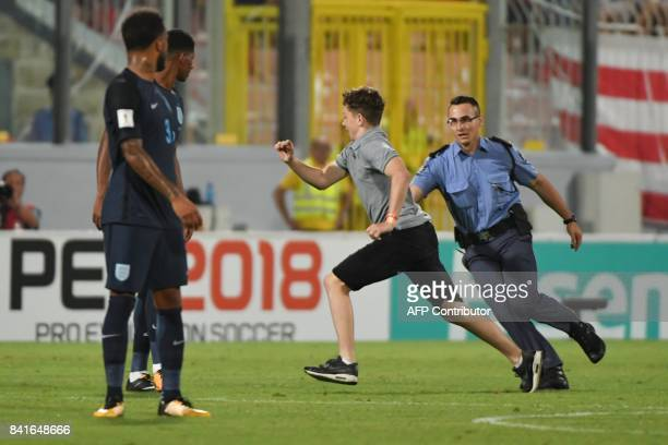 A young man runs away from a policeman during his pitch invasion as part of the 2018 FIFA World Cup qualifying football match Malta vs England at the...