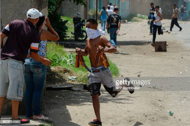 A young man runs carryng stolen alcohol bottles after looting a supermarket in Maracay Aragua state Venezuela on June 27 2017 / AFP PHOTO / Federico...