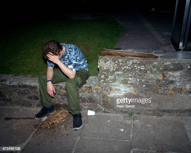 A young man sat on a wall feels the effects of a night out in Newquay Cornwall July 2001