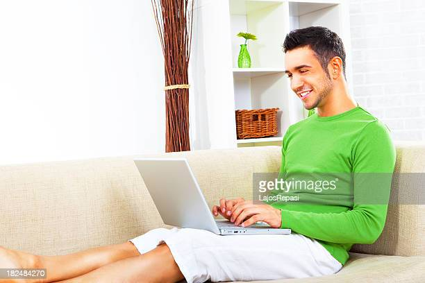 Young man sat on sofa working on his laptop
