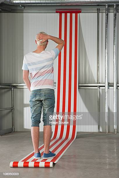 Young man scratching head, striped wallpaper on wall