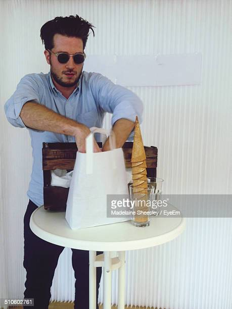 Young man searching something in bag with ice cream cones on table
