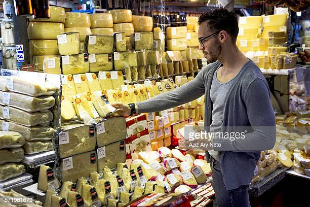 Young man selecting cheese in delicatessen market stall, Sao Paulo, Brazil