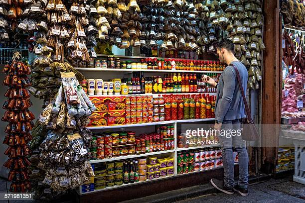 Young man selecting spices in market stall, Sao Paulo, Brazil