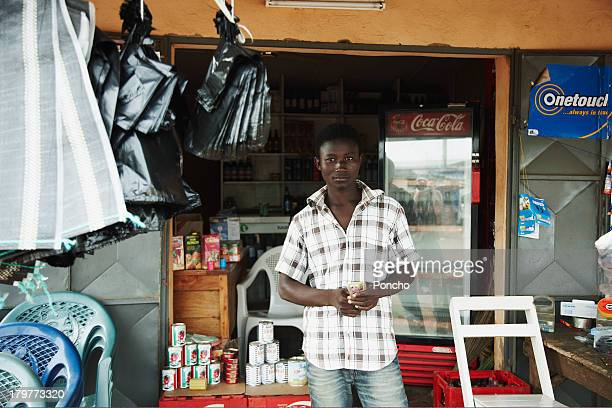 young man selling phone cards in front of his shop