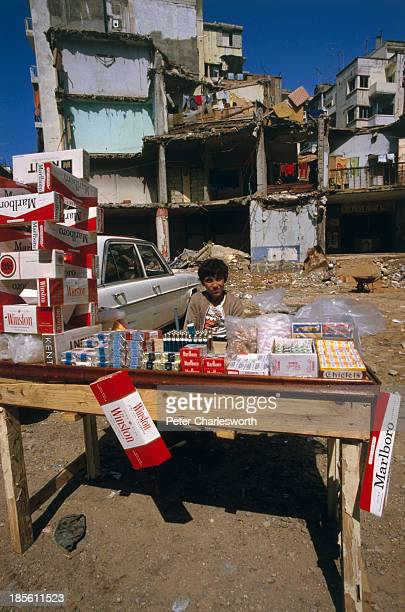 A young man sells cigarettes chewing gum and lighters from an improvised streetside stall during a lull in the fighting against a background of...