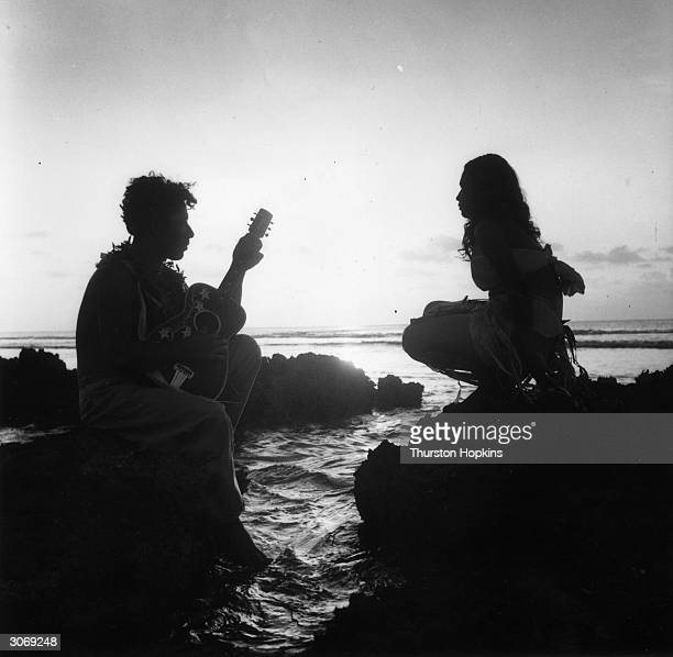 A young man serenades his sweetheart with a guitar on a rocky promontory of Tonga an island in the Pacific Ocean Original Publication Picture Post...