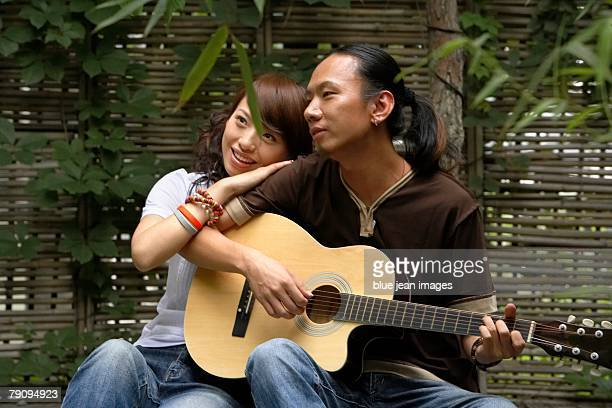 A young man serenading a young woman on his guitar.