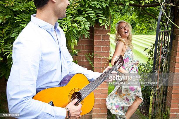 Young man serenading woman in garden