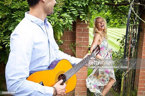 Young man serenading woman in garden