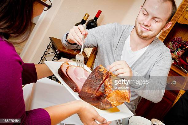 Young Man Serving Ham at Holiday Dinner