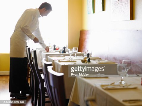 Young man setting tables in restaurant, side view