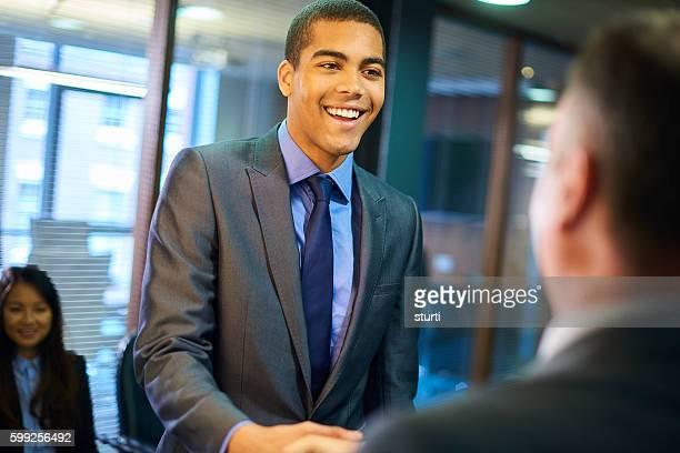 Junger Mann schüttelt Hände mit seinen potenziellen neuen Chef