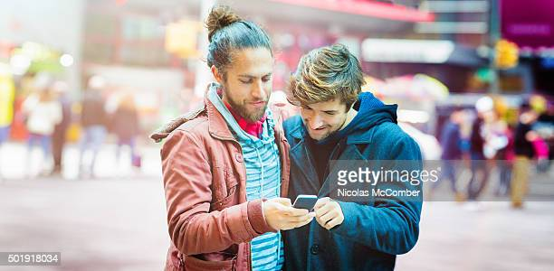Young man sharing media with friend using mobile phone panorama