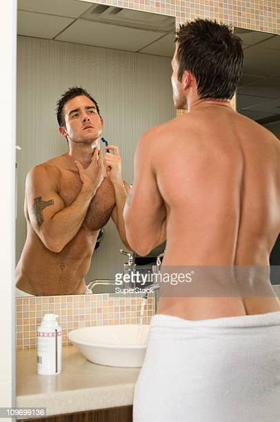 Young man shaving in bathroom