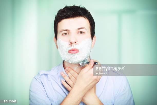 Young man shaving in the bathroom