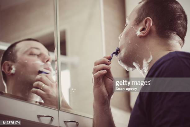 Young man shaving with razor