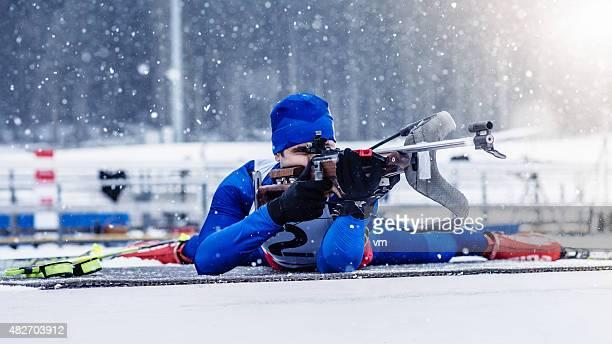 Young man shooting at biathlon training