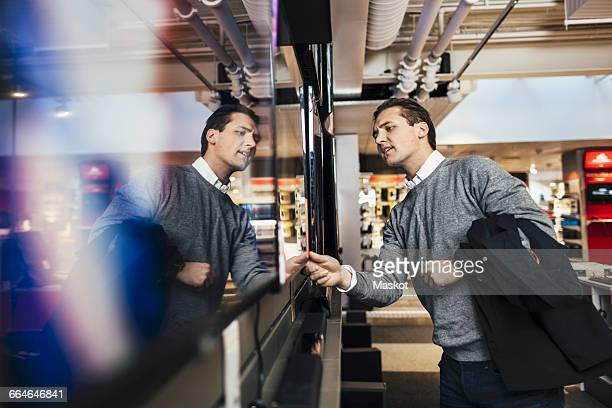 Young man shopping for television in electronics store