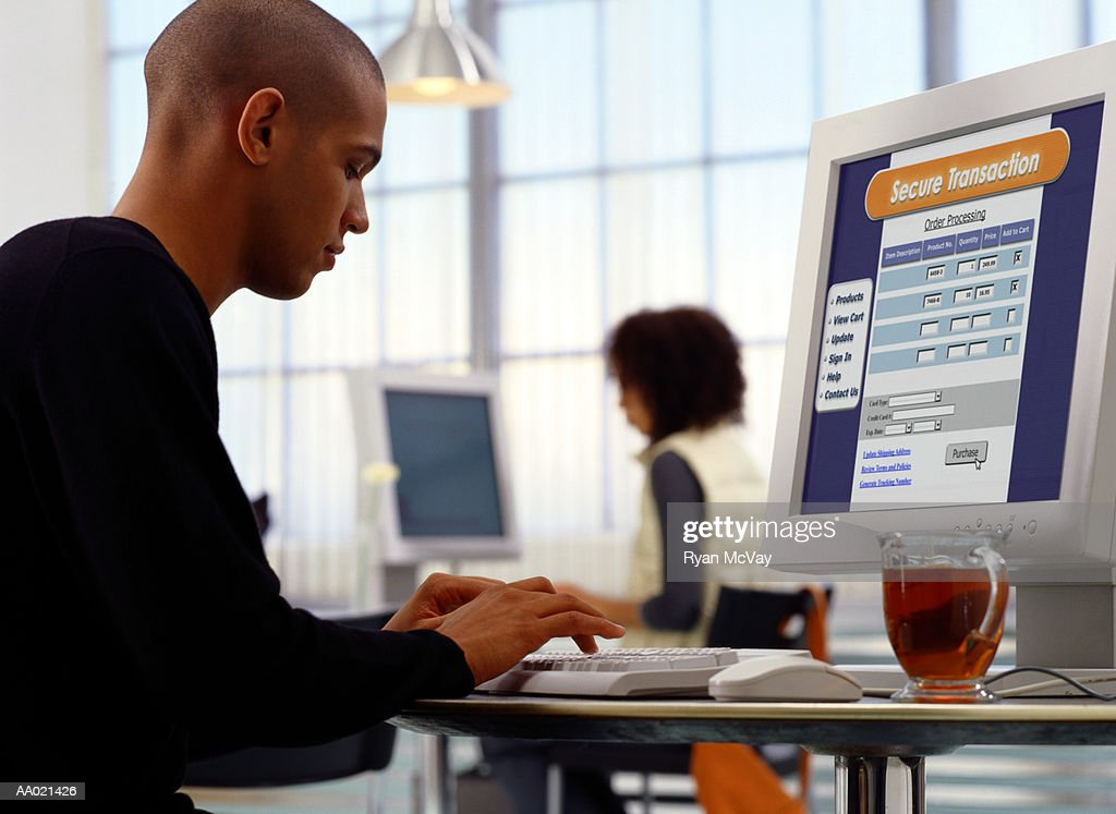 Young man shopping on ecommerce site at internet cafe