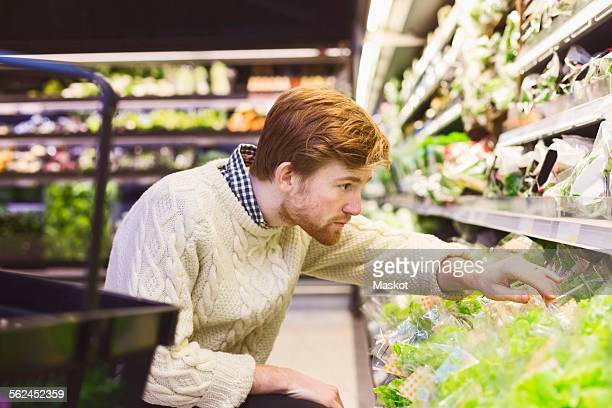 Young man shopping vegetables at supermarket
