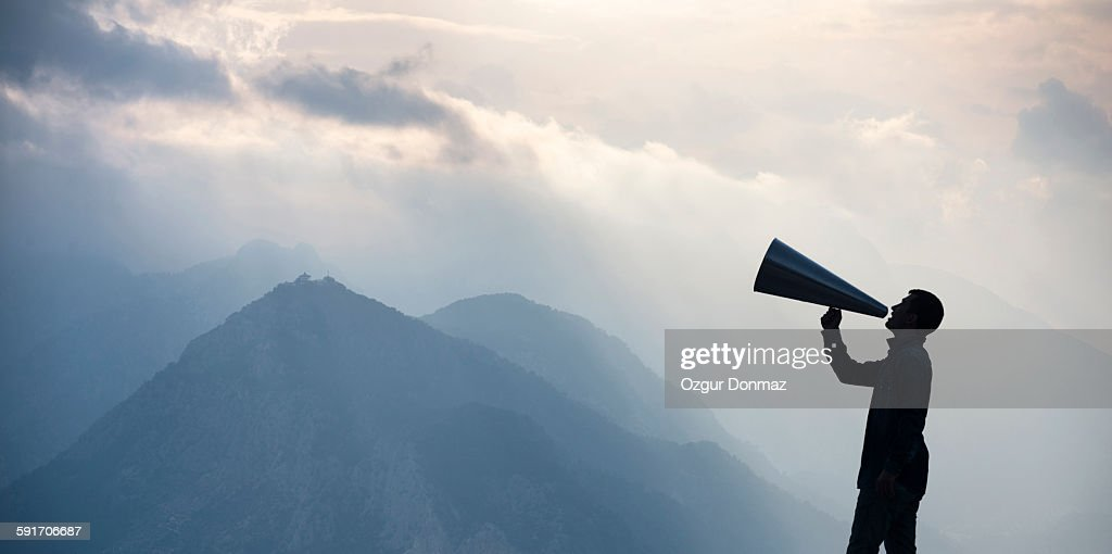Young man shouting into megaphone : Stock Photo