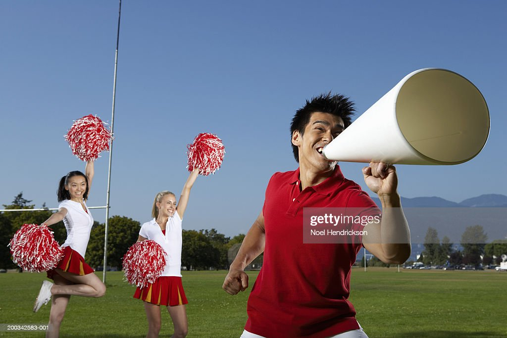 Young man shouting through megaphone near young female cheerleaders : Stock Photo