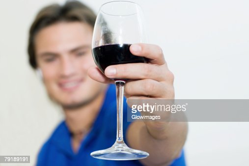 Young man showing a wine glass and smiling : Stock Photo