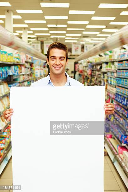 Young man showing blank board at super market